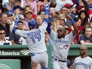 José Bautista (19) celebra con su compañero José Reyes, segundo a la derecha, tras conectar un jonrón para los Azulejos de Toronto en el sexto inning ante los Medias Rojas de Boston