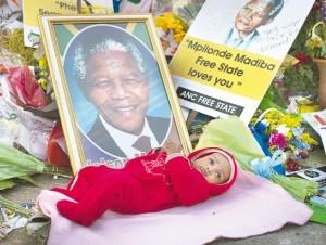Un bebé fue colocado junto a fotos y flores en honor del expresidente sudafricano.