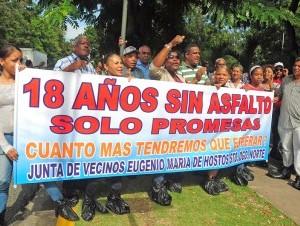 Con fundas negras cubriendo sus pies, moradores del Eugenio María de Hostos, en Santo Domingo Norte, reclamaron la construcción de aceras, contenes y asfaltado de sus calles.