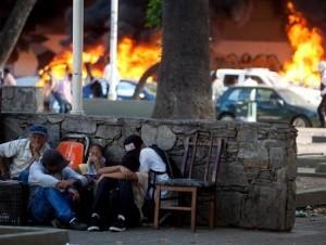 Gente se protege de acciones violentas mientras al fondo se observan vehículos que fueron incendiados durante disturbios ocurridos en una manifestación de opositores en Caracas, Venezuela, el miércoles 12 de febrero de 2014.