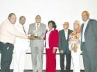 """El director ejecutivo del INDRI, Olgo Fernández, recibe el máximo galardón como el """"Fronterizo del año 2014"""". Le hacen la entrega directivos de la fundación."""