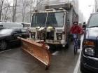 Un ciclista pasa entre automóviles estacionados en la Sexta Avenida de la ciudad de Nueva York y un camión de basura con una pala añadida para retirar nieve, el lunes 26 de enero de 2015.