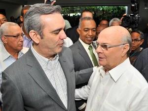 Hipólito y Luis se saludan al coincidir en el velatorio de la dirigente del PRM, Ana María Acevedo, en la funeraria Blandino.