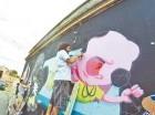 """Poteleche junto a su equipo trabajan en el mural """"Hoy Santa Bárbara"""", en la Zona Colonial, un proyecto en el que participan artistas nacionales e internacionales."""