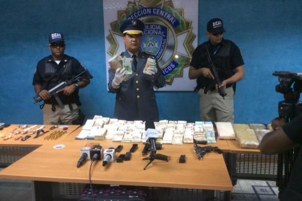 El coronel Jacobo Mateo Moquete muestra el dinero y armas incautados a banda dirigida por excapitán de la Armada.